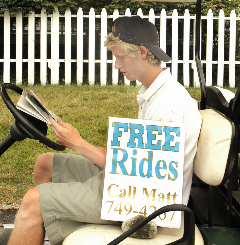 Matt Rand waits in his golf cart to provide rides on Peaks Island.