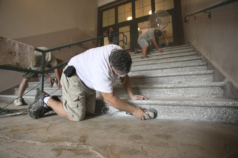 Tony Celeste, owner of Tony's Tile, uses a diamond grinder to remove excess cement during the restoration of the terrazzo tile stairs in the front entrance of Portland High School.
