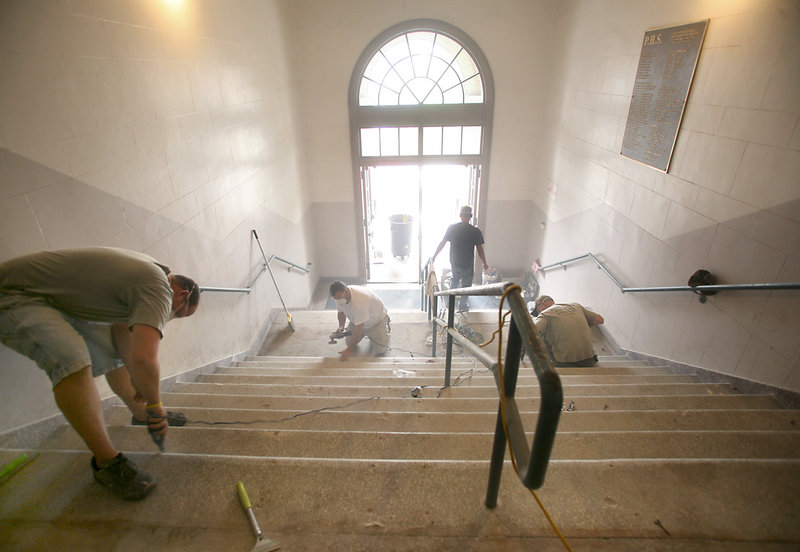 """Workers restore the terrazzo tile stairs last week in the foyer of Portland High School. """"This is a work of art,"""" said Tony Celeste, the contractor who is restoring the finish after removing cement, rusted steel and rubber tread that had covered the stairway for more than two decades."""