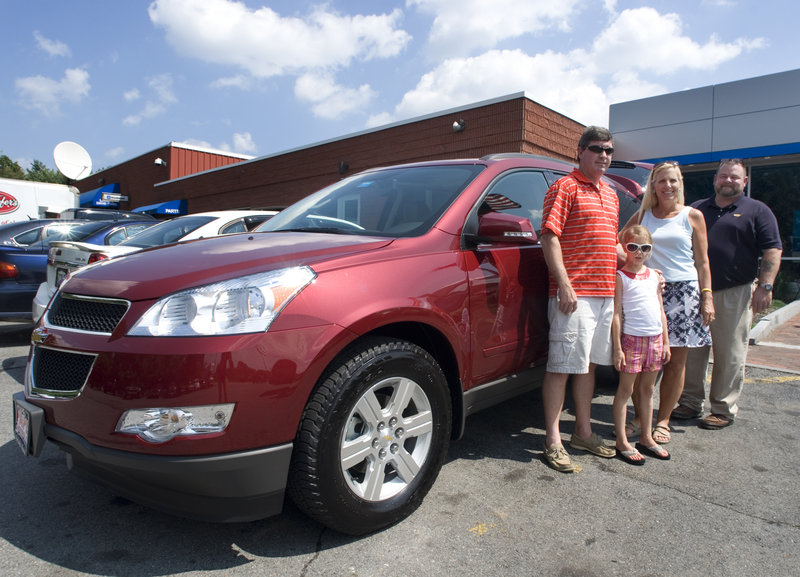 Todd and Dawn Flaherty and their daughter, Brooke, stand in front of their newly purchased 2010 Traverse crossover SUV with sales manager Russ Rogers at Pape Chevrolet in South Portland.
