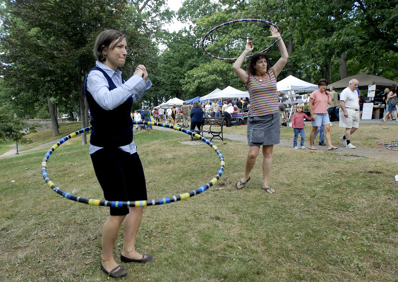 Hannah Fogg of Portland tries hula hooping with Tracy Tingley during the Portland Farmers Market at Deering Oaks on Saturday.