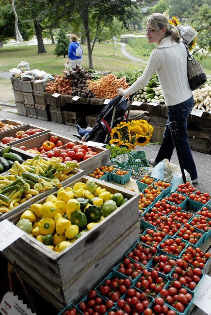 Rebecca Ermlich looks over the produce at Freedom Farm's display at the farmers market at Deering Oaks recently.