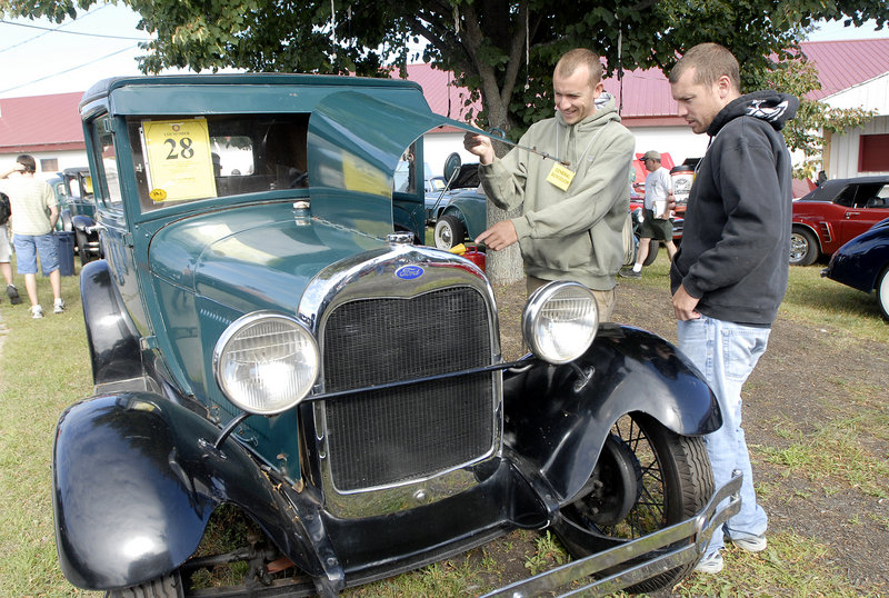 Tim Hayes, left, and Andrew Hayes, both of Gray, look over a 1921 Ford Model T prior to the auction Saturday. The car was one of more than 100 in Phil Hall's collection that went on the auction block, taking in a total of more than $1.3 million.