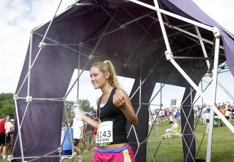 Rose Marie Parry of Ponte Vedra Beach, Fla., cools off in the mist tent after finishing the race. Parry, 16, had an official time of 56 minutes, 7 seconds.