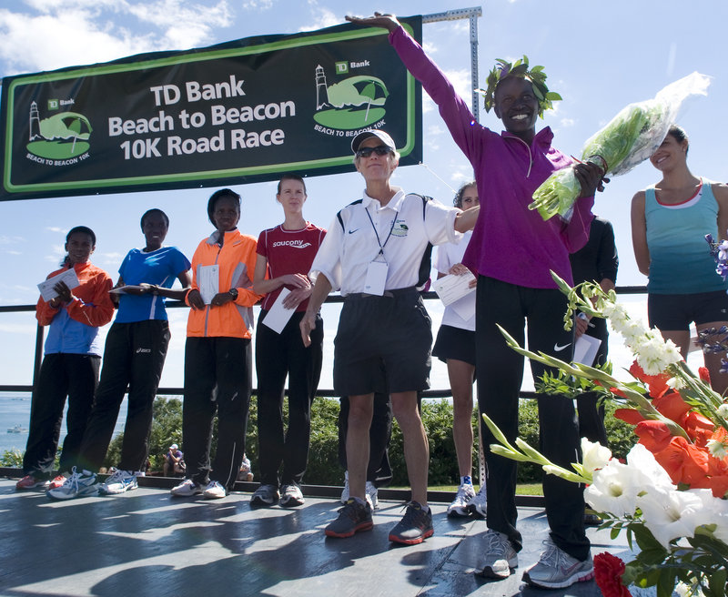 Lineth Chepkurui of Kenya waves to the crowd from the awards stage as race founder Joan Benoit Samuelson looks on. Chepkurui set a women's course record with her time of 30 minutes, 59.4 seconds, smashing the mark of 31:25.8 set by Alevtina Ivanova of Russia in 2006.