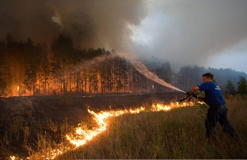 A firefighter battles a wildfire last week near the village of Dolginino, Russia. Climate scientists want better computer modeling to predict weather havoc like this summer's heat wave in Russia and floods in Pakistan. They will discuss such tools in meetings this month and next in Europe and the United States.