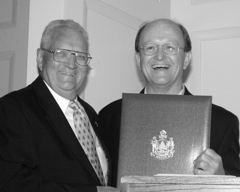 An unidentified legislator joins James E. Clark, left, as Clark is recognized by the Maine Legislature on his 80th birthday in 2003.
