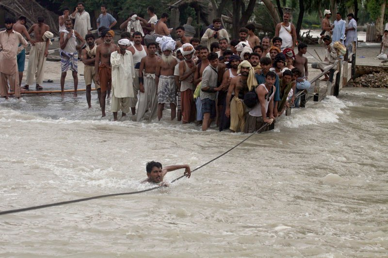 A man crosses a canal Monday with the help of a cable from an inundated bridge in Ghazi Gat, Pakistan. The number of people affected by Pakistan's floods exceeds 13 million – more than the combined total of the 2004 tsunami and the 2005 Kashmir and 2010 Haitian earthquakes, the U.N. said.