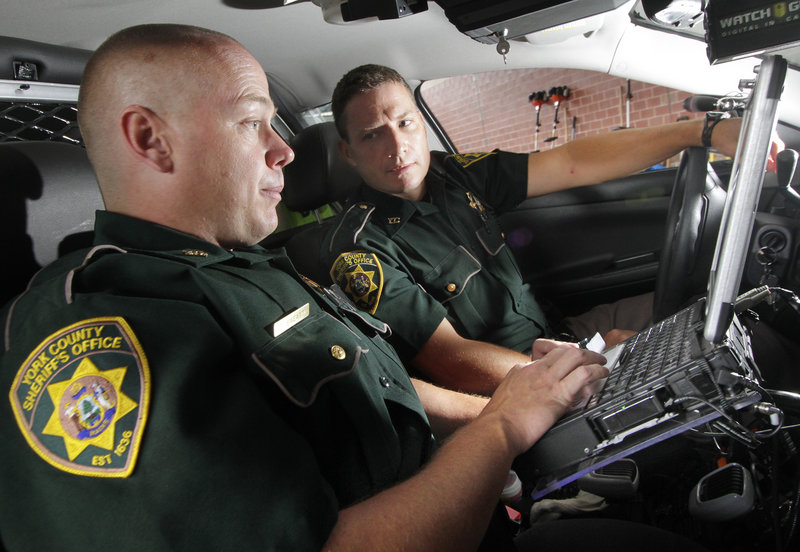 Deputy Corey Sweatt, left, trains Thomas Searway, one of four new York County Sheriff's Office deputies, to use the vehicle computer on Monday. The department is now screening applicants for the last vacant deputy position, which will bring the department up to its full strength of 24.