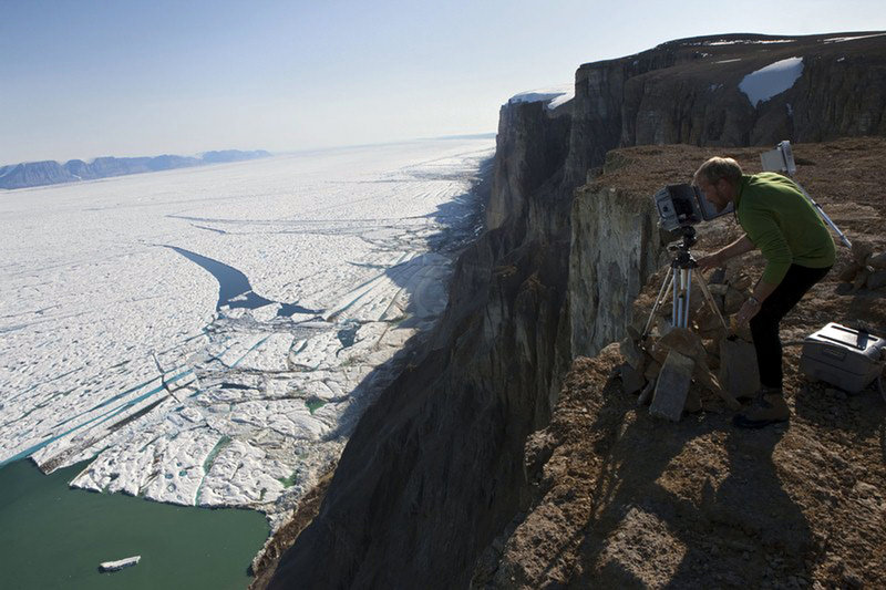 In a July 6, 2009, photo made available by Greenpeace, researcher Jason Box adjusts a time-lapse camera on the southeast side of Petermann Glacier, one of Greenland's largest and most northerly glaciers. A 100-square-mile iceberg broke off the glacier last week.