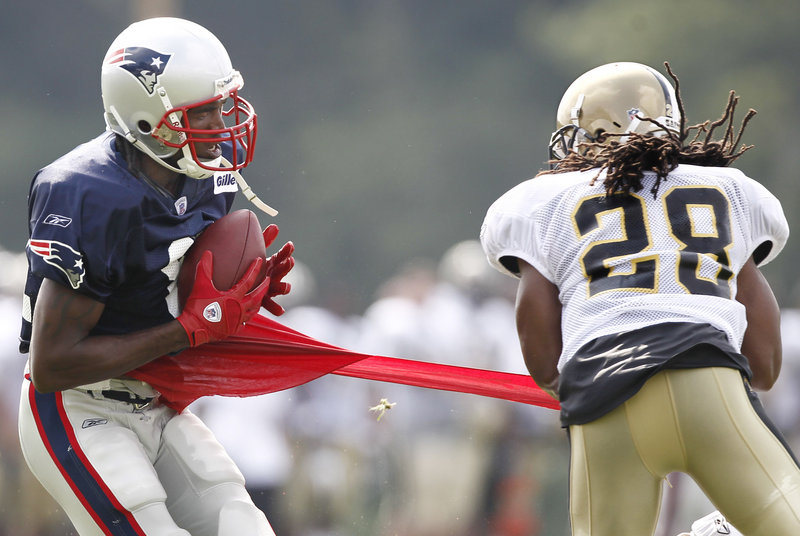 Patriots receiver Randy Moss, left, reels in a pass Tuesday as Saints safety Usama Young rips his shirt during a joint practice in Foxborough, Mass. The teams open their preseason schedules Thursday night at Gillette Stadium.