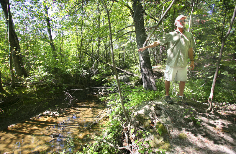 Jeff Dennis, a state biologist, discusses the progress of the restoration of the Long Creek watershed during a tour in South Portland on Tuesday. He said large amounts of runoff have carved a deep channel on the main stem of the creek.