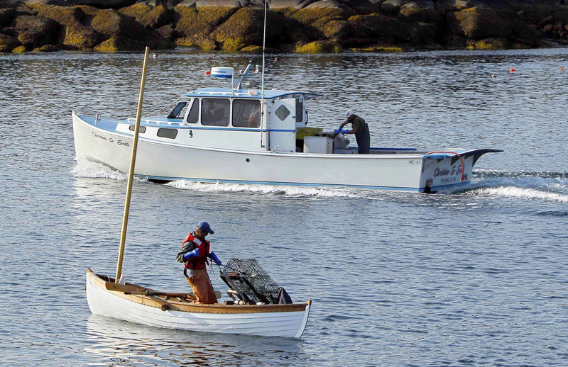 """Nat Hussey hauls a trap by hand as a diesel-powered lobsterboat motors by. Hussey calls the effort his """"zero-carbon lobstering project."""""""