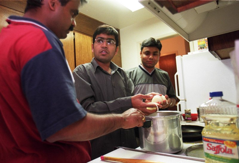 Pratap Yeware, left, Deepak Jaware, center, and Sudhir Wath share an apartment with two other men from India working in the U.S. on H1B visa status. A bill in Congress would raise visa fees for foreign workers.