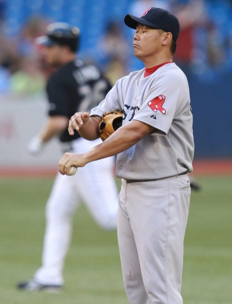 Daisuke Matsuzaka stands on the mound as the Blue Jays' Adam Lind rounds the bases following a solo home run in the second inning Tuesday night in Toronto.