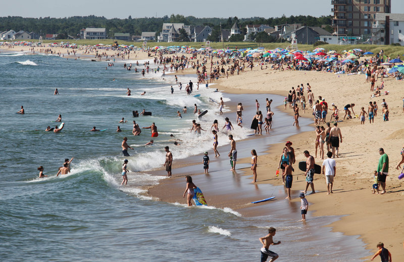 Swimmers and sunbathers enjoy another hot, sunny day. Swimmers can help protect themselves from rip currents by checking with lifeguards on surf conditions.