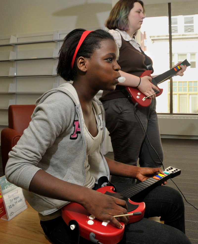 Christina Mahounou, 13, left, and Sasha Leppanen, 13, play Guitar Hero III during game night Wednesday at the Portland Public Library.