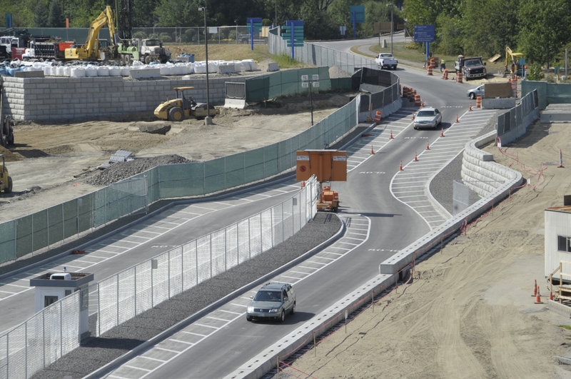 A median strip divides the access road into two sets of lanes, one set that will serve a new departure area and the other set to take drivers to a passenger pickup area.