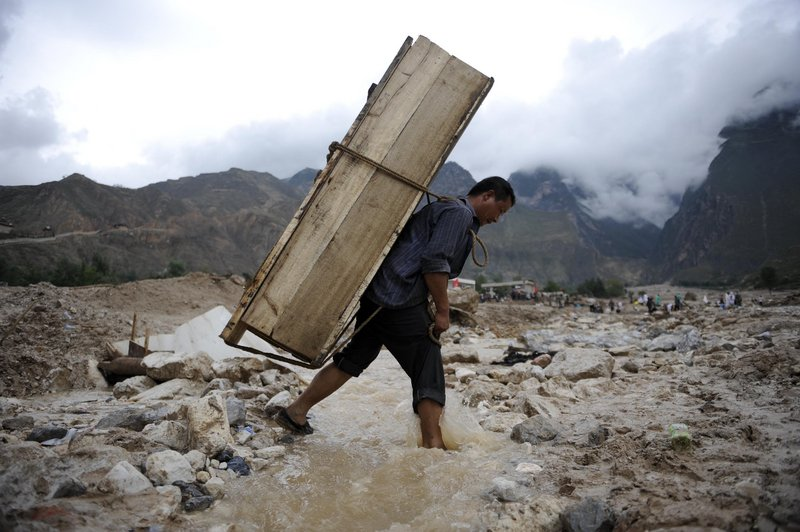 Wang Xidai carries a coffin that will be used for his niece who was killed after a mudslide swept through the town of Zhouqu in China's Gansu province on Thursday.