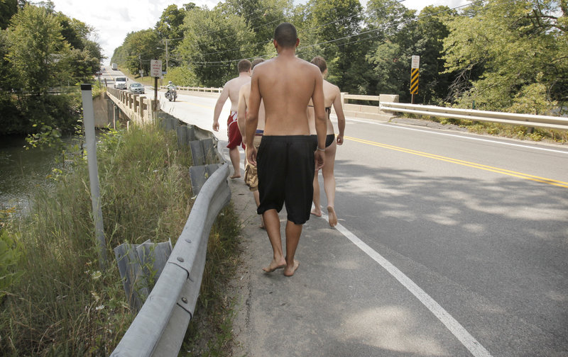 """Youths return for another dive from the bridge. Last summer a swimmer was hit by a car and nearly killed while crossing the bridge to jump off. Buxton Police Chief Michael Grovo said there's also a concern about drinking there. """"Drinking adds fuel to the fire. The kids get more daring,"""" he said. """"It's a constant problem down there."""""""