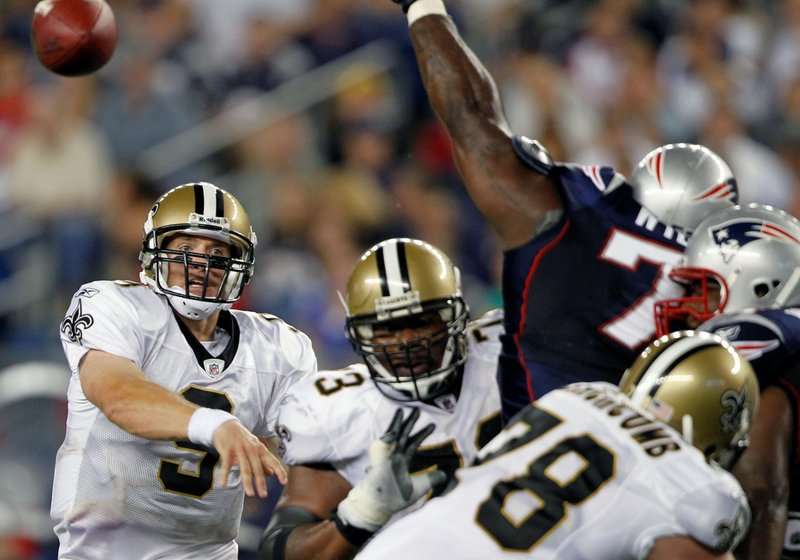 Saints quarterback Drew Brees, left, lets a pass fly as New England nose tackle Vince Wilfork fights off blockers and tries to deflect the ball. Brees was 9 for 13 for 55 yards in limited action in the exhibition opener at Foxborough, Mass.