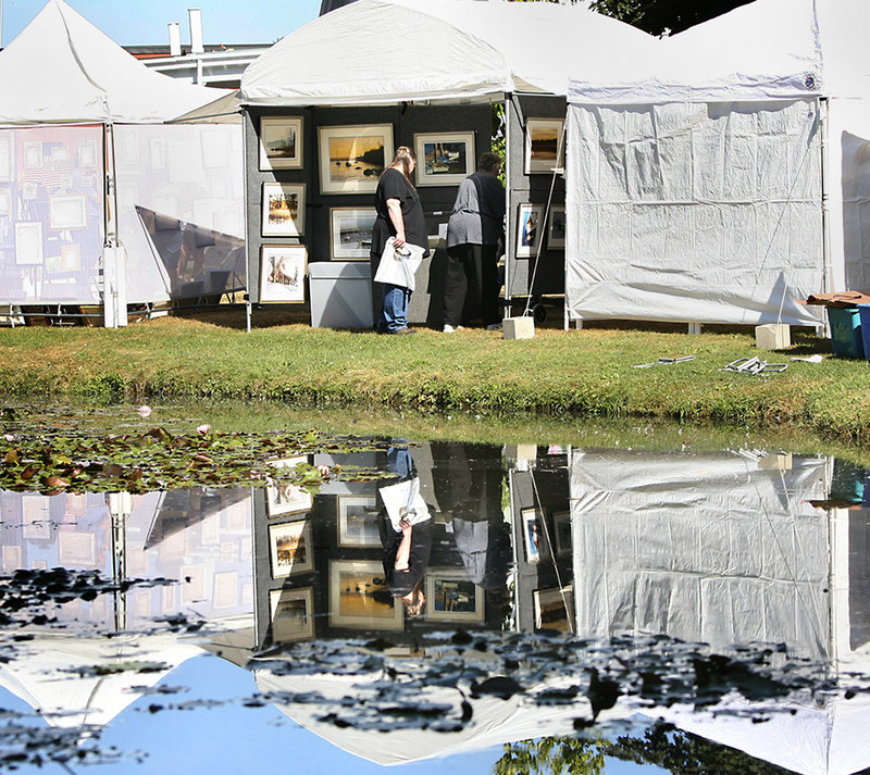 Shelley Fisher, left, and her mother Anne are reflected in Mill Creek Pond as they look at watercolors painted by Denis Leblanc of Auburn during the 31st annual South Portland Art in the Park at Mill Creek Park on Saturday.
