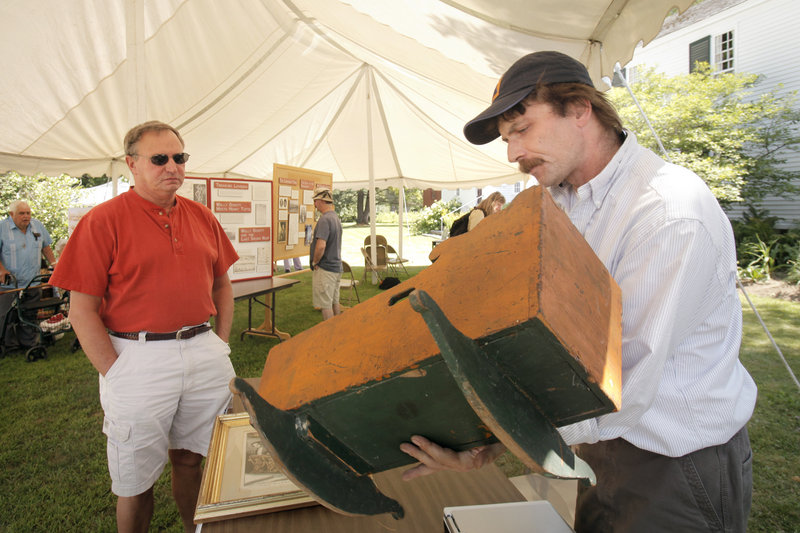 Jay Boschetti appraises a cradle owned by Ray Harris, left, and his wife Maureen during the festival. Boschetti owns Steam Mill Antiques in Bethel.