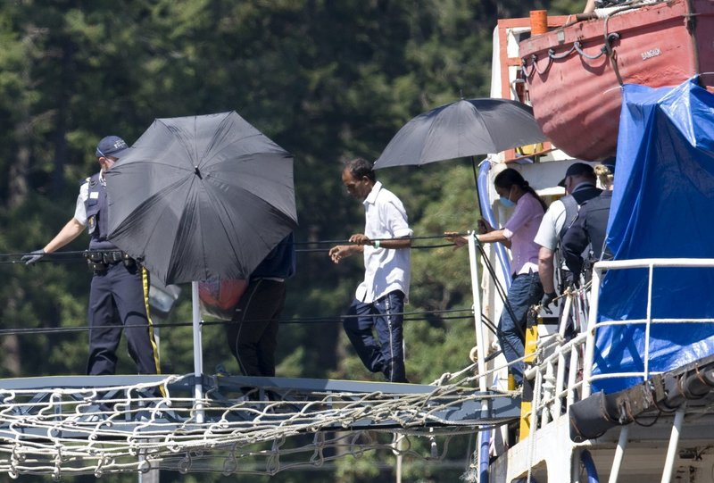 Tamil refugees are escorted off the MV Sun Sea by Canadian officials in Colwood, B.C., on Friday. Canada is home to the largest Tamil community outside Sri Lanka and India.