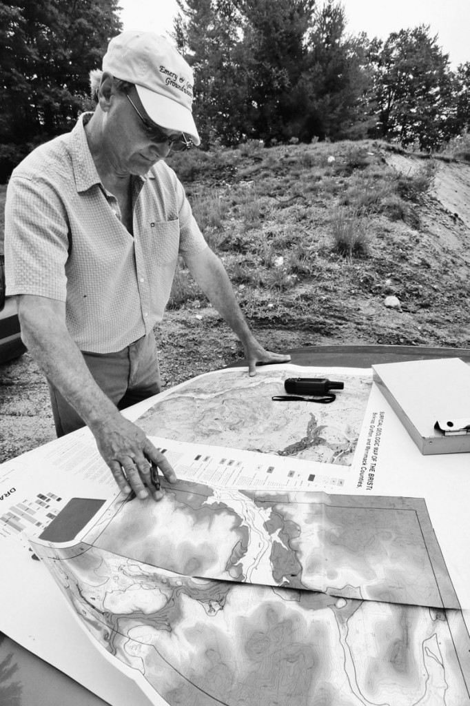 Geologist John Brooks checks on maps in New Hampton, N.H.