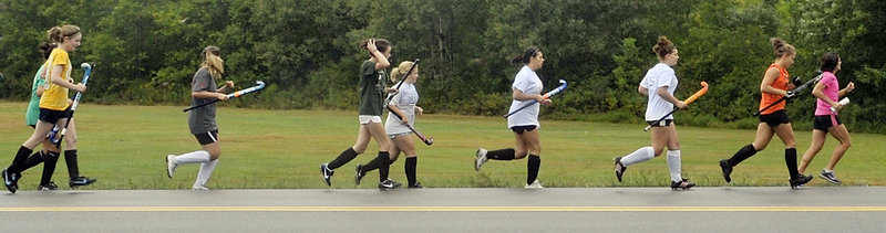 Biddeford field hockey players go for a run with their new coach, Leslie Mourmouras, leading the way. Mourmouras also coaches track and field and previously was Biddeford's cross country coach.