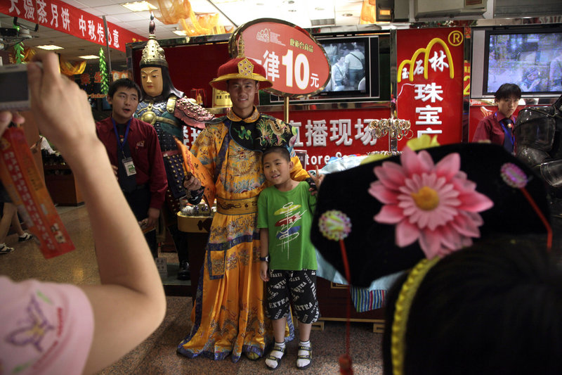 A man dressed as a Chinese emperor poses for photos Monday to promote a shop in Beijing. Japan lost its place as the No. 2 economy in the second quarter as receding global growth sapped its momentum.