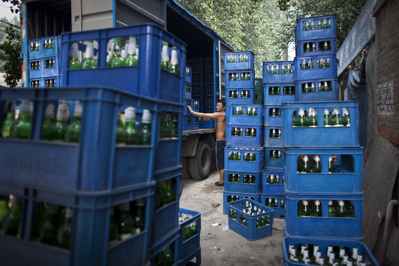 A worker takes a break near a truck Tuesday while loading packs of beer bottles in Beijing. China's 1.3 billion people had an average income of $3,600 last year.