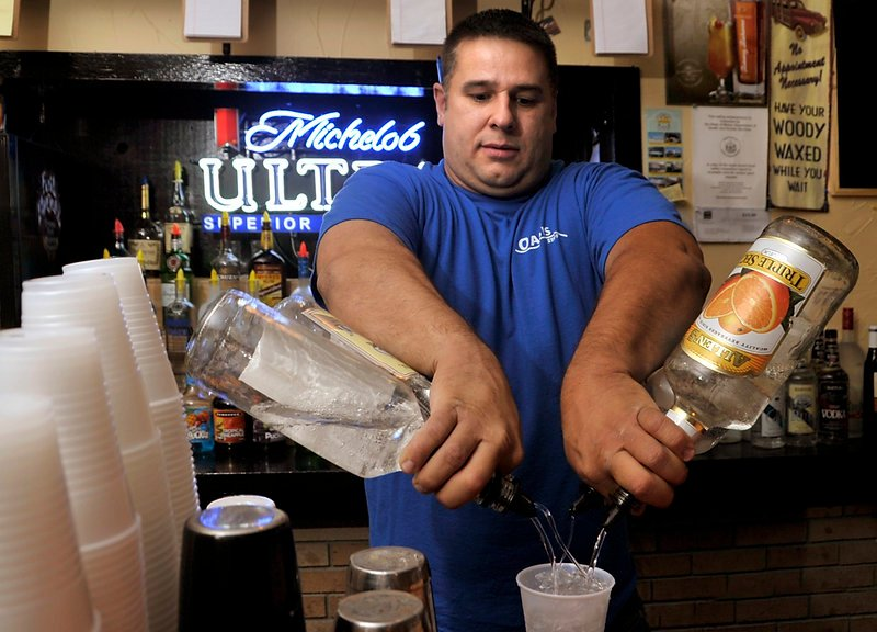 Chris Steele, co-owner and bartender at the Oasis, mixes up the house special, the Oasis Punch.