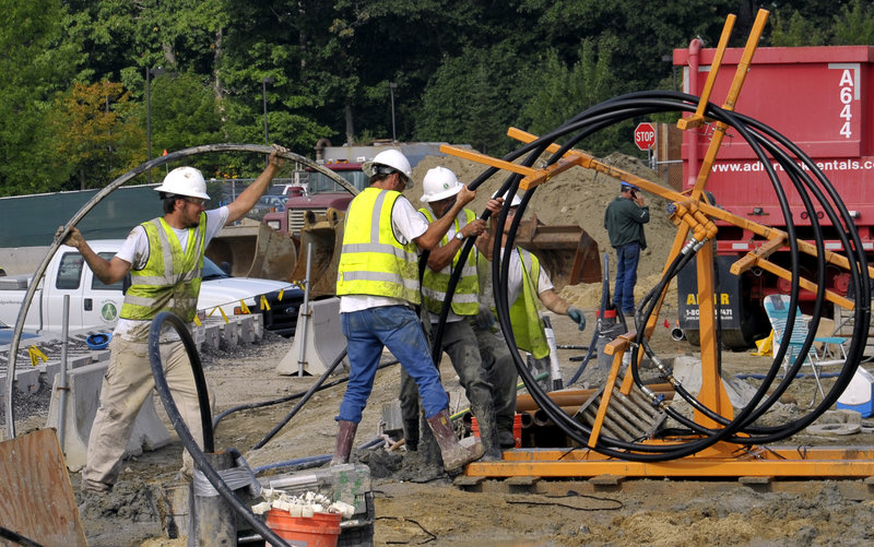 "Workers push 1,000 feet of high-density polyethylene pipe into one of 120 500-foot drilled holes that will be one ""loop"" of the geothermal system being installed to help heat and cool the Portland International Jetport's expansion when it opens in 2012."