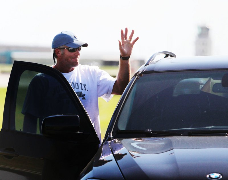 Brett Favre waves to the media and fans Tuesday after arriving by a private jet at Flying Cloud Airport in Eden Prairie, Minn., to rejoin the Vikings in training camp.