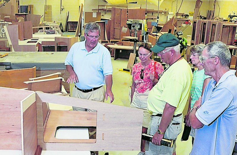 Bentley Collins, left, vice president of marketing and sales at Sabre Yachts in Raymond, explains the company's processes to a tour group Tuesday. The group includes, left to right, Ginnie and Chuck Hurley, both from Annapolis, Md., and Joyce and Richard Knight of North Yarmouth.