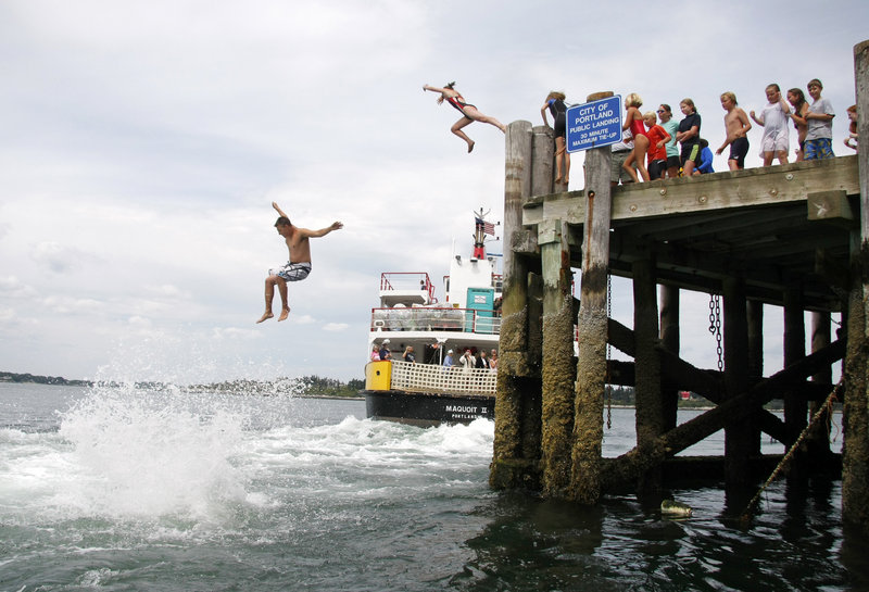 """Participants take the """"Big Jump"""" off the dock on Cliff Island into the wake of a Casco Bay Ferry vessel as it departs just after noon Wednesday. The total number of jumpers fell far short of the record for the annual summer tradition."""