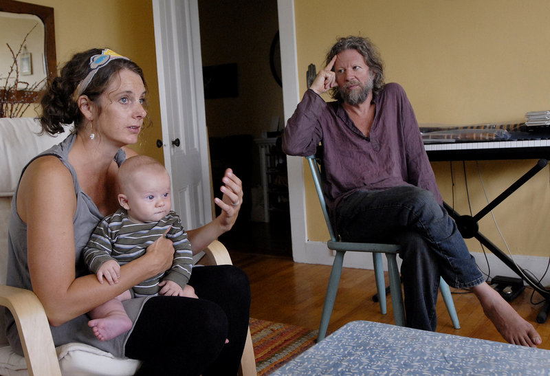 Lara Schneider shares her story while holding her son Julian in the family's Portland apartment. At right is her husband, flutist Phil James, who is recovering from a stroke.