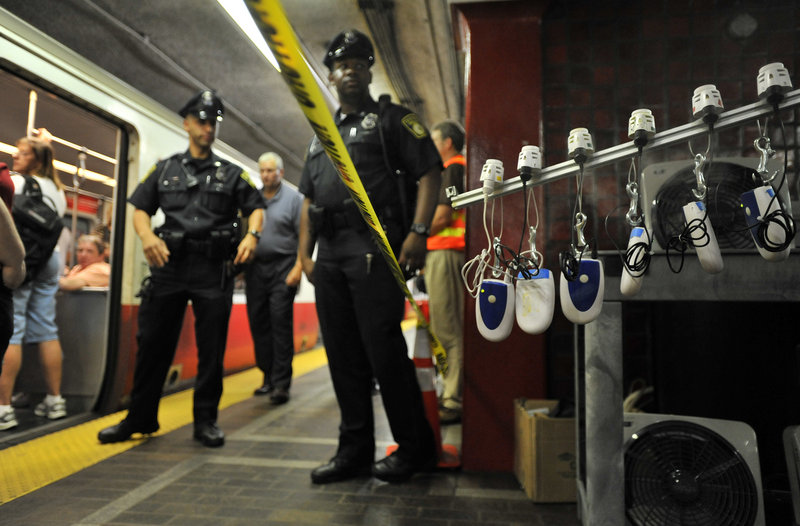 MBTA police officers and passengers look on as a machine releases gases and fluorescent particles Friday, during an exercise in Boston's Park Street Subway station. Scientists released the gases and fluorescent particles to study how toxic chemicals and lethal biological agents could spread through the nation's oldest subway system in a terrorist attack.