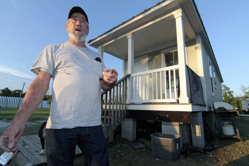 Pete Yarborough speaks in front of his 400-square-foot cottage in Lakeshore, Miss. He can buy the cottage for $351, but it would cost about $23,000 to raise it in the flood-prone area. If he doesn't buy it, the state will evict him.