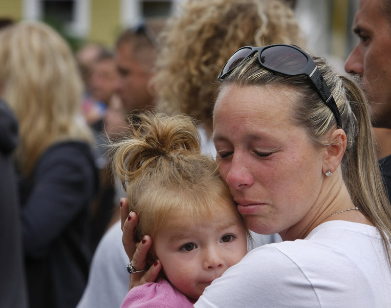 Pam Maxon of Wells holds her daughter Payton, 2, while listening to the names of 65 fallen soldiers being read before the start of the run.