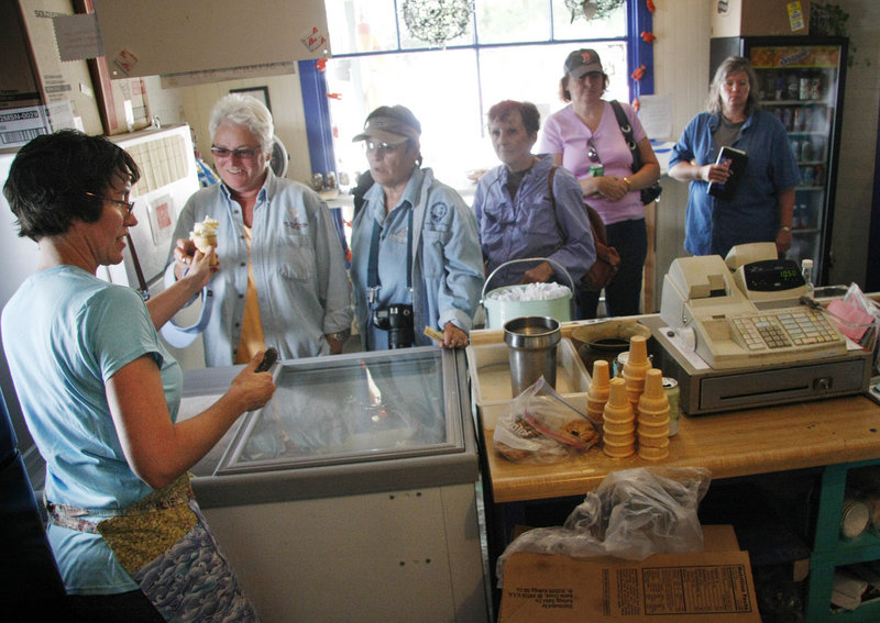 Johanna Corman serves ice cream and other treats to a crowd of ferry passengers at Pearls Seaside Market on Cliff Island. The Cormans bought the store two years ago.