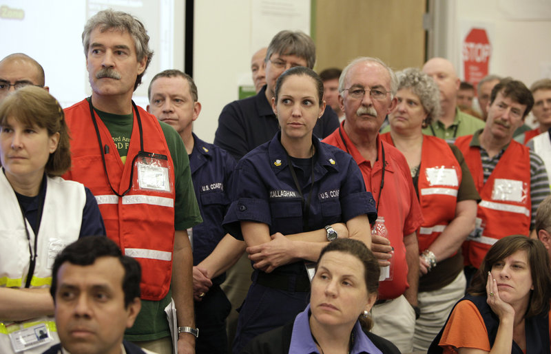 On June 12, BP employees and members of the Coast Guard at the Houma, La., Joint Information Center listen to BP Chief Operating Officer Doug Suttles speak about the Deepwater Horizon oil spill. BP and Coast Guard employees also sat side-by-side at a command center in Robert, La.