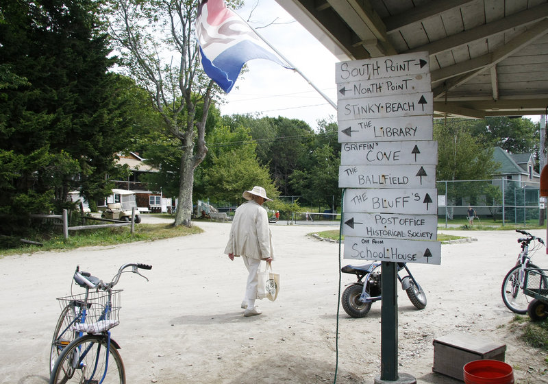 """After shopping for eggs and sugar, Eva Alming, a Cliff Island summer resident since the 1930s, walks past hand-written directional signs posted outside Pearls Seaside Market. """"He's the best store we've ever had,"""" said Alming."""