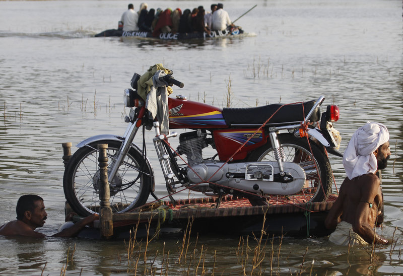 Men push a motorcycle on rubber floats Monday as a police boat passes along a flooded road in Baseera, Punjab province, Pakistan. President Asif Ali Zardari compared anger at the government to the anti-government sentiment generated by the aftermath of Hurricane Katrina in the U.S.