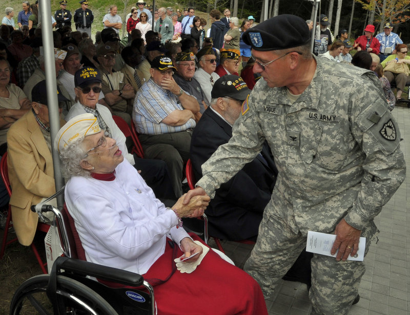 Marie Clancy, left, who is credited with keeping alive the idea of a military cemetery in southern Maine, is thanked by Col. Valmore Vigue, chaplain for the Maine Army National Guard, before the dedication of the Southern Maine Memorial Veterans Cemetery in Sanford on Tuesday. The main road into the cemetery will be named for Clancy.