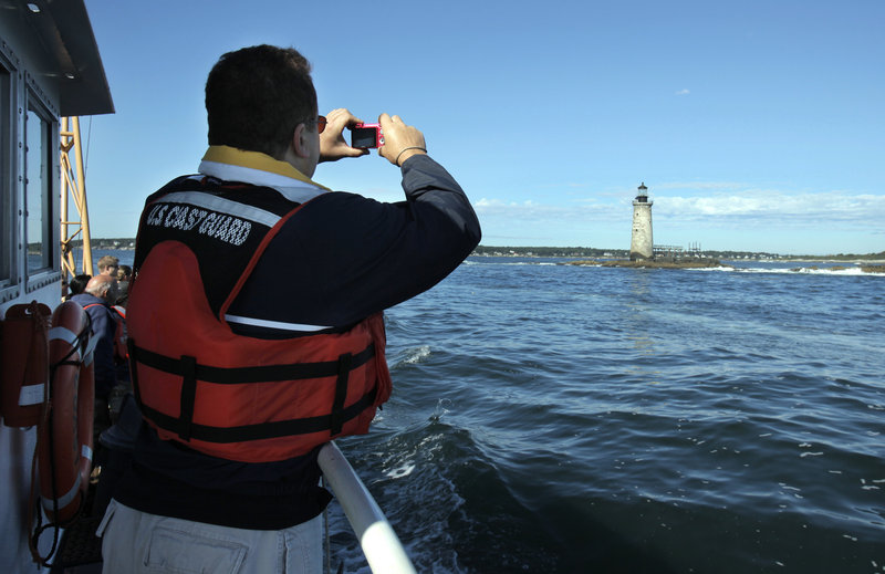 Scott Raspa of Cape Elizabeth, a registered bidder, takes a photo of Ram Island Ledge Light on Thursday. He said the mystery and history would make it interesting to own a lighthouse.