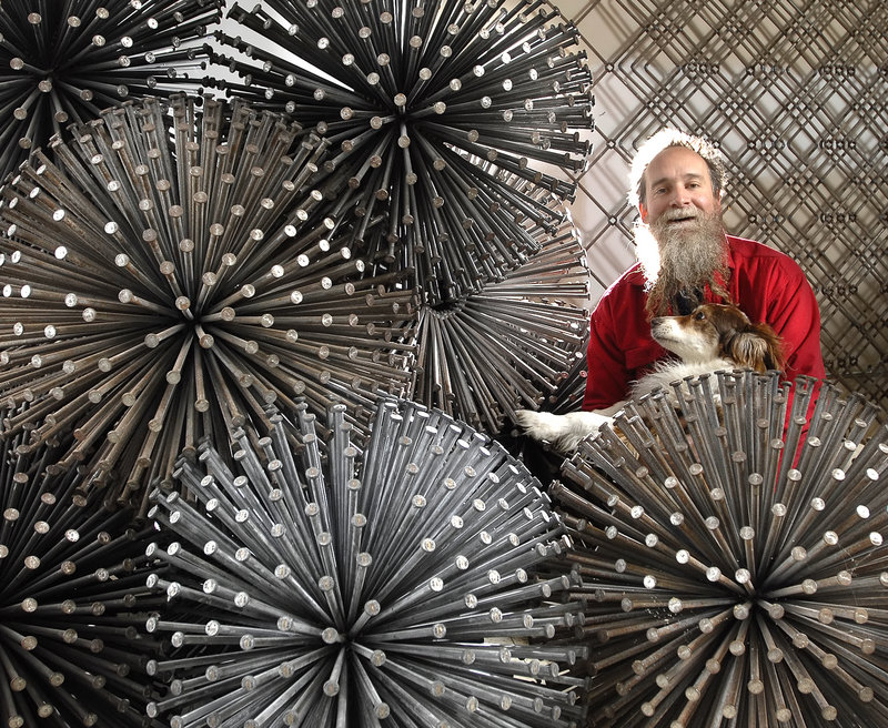 John Bisbee poses with some of his nail sculptures for a 2008 exhibition of his work at the Portland Museum of Art.