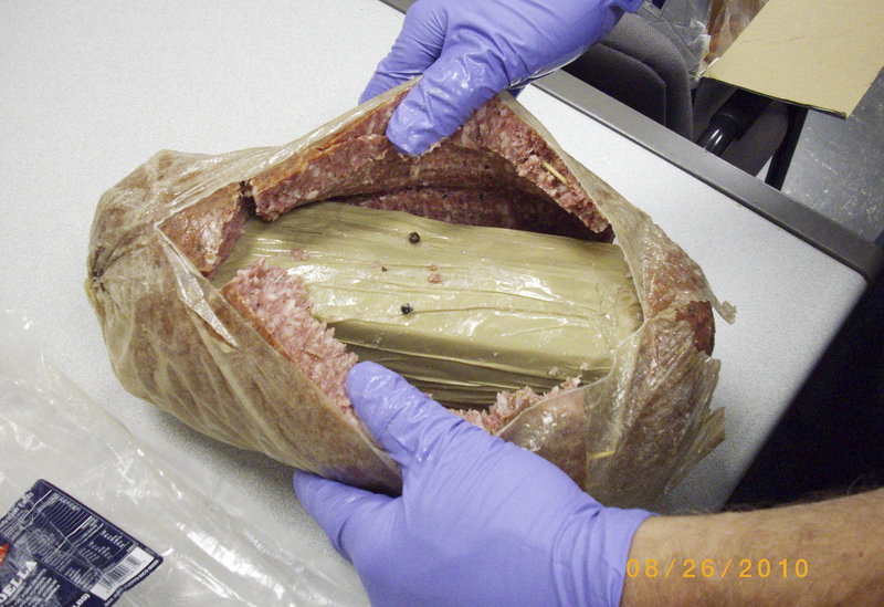 A Holyoke, Mass., police photo shows a kilogram of cocaine hidden in a hollowed-out chunk of bologna.