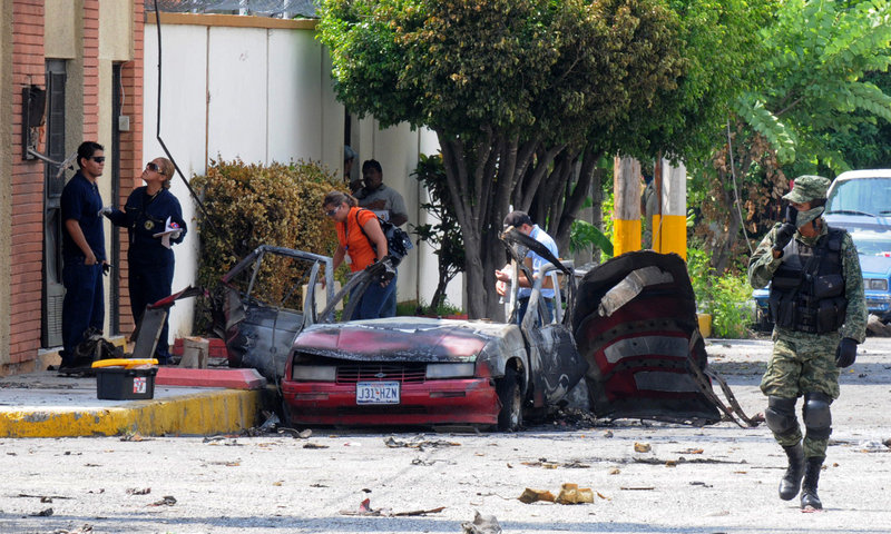 Investigators probe the site of one of two vehicle explosions Friday in Ciudad Victoria, Mexico, in a northern state where officials are also investigating the massacre of 72 Central and South American migrants. Nobody was injured in the explosions.